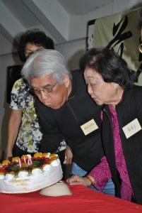 白垚及严汉平在朋友们的祝福下点燃结婚周年庆的蛋糕